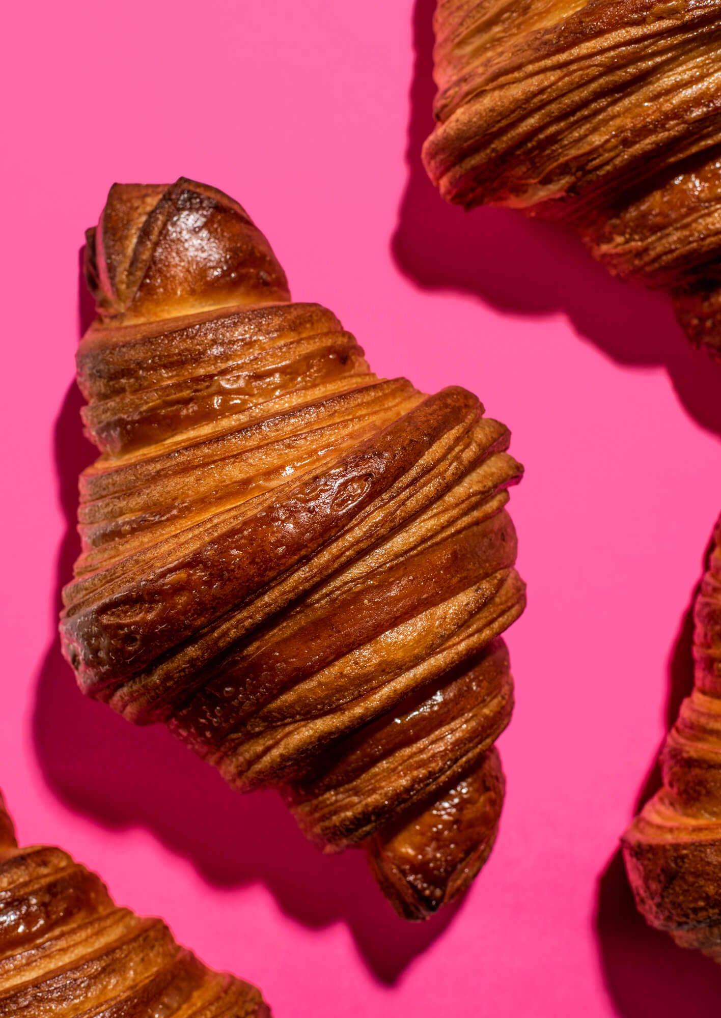 perfect crispy vegan croissants on pink background