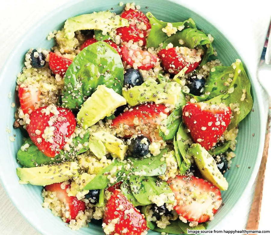 quinoa salad in bowl with berries spinach and avocado