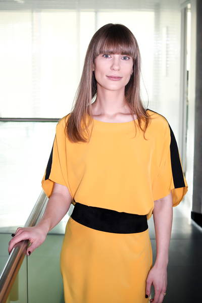 Cyrille Polla standing in yellow dress with long brown hair with bangs, soft smile
