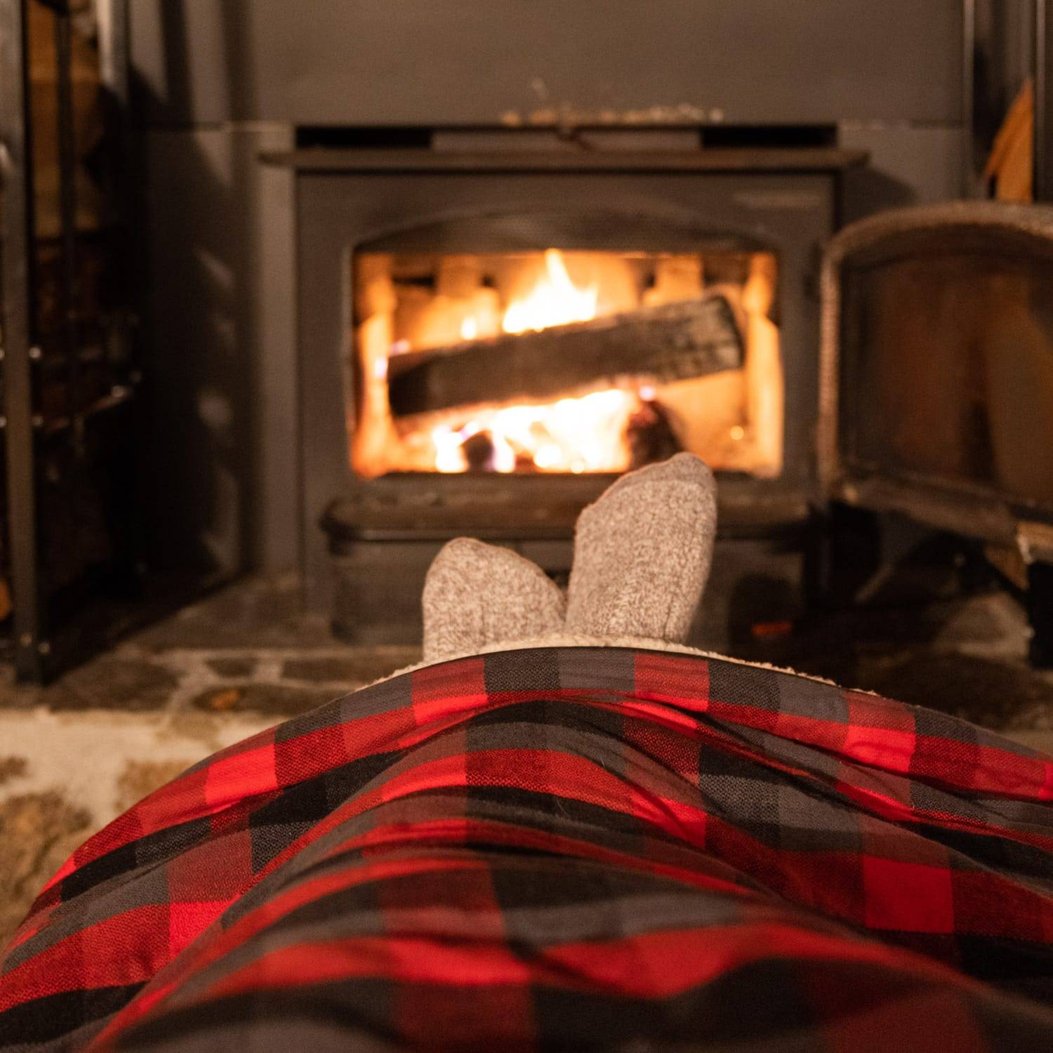 Feet under a flannel throw blanket in front of a fireplace