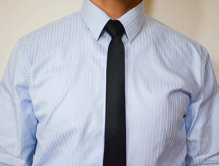 Man wearing a black skinny tie and blue dress shirt