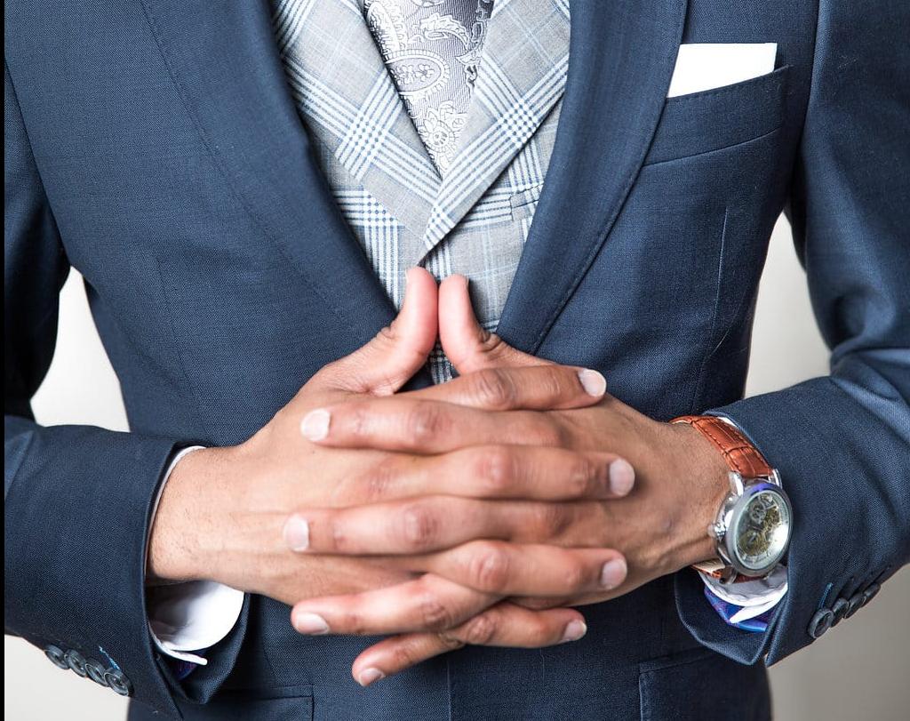 Man in bespoke navy suit folds hangs to show off luxury watch