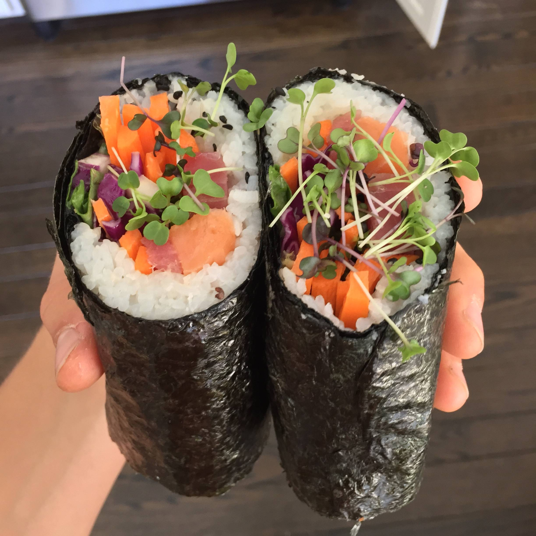 Sushi burrito with seaweed outside, rice inside, and sashimi salmon, tuna, sliced carrots, and daikon radish microgreens.