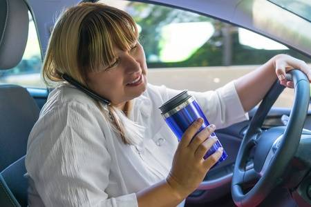 Woman driving car distracted by phone