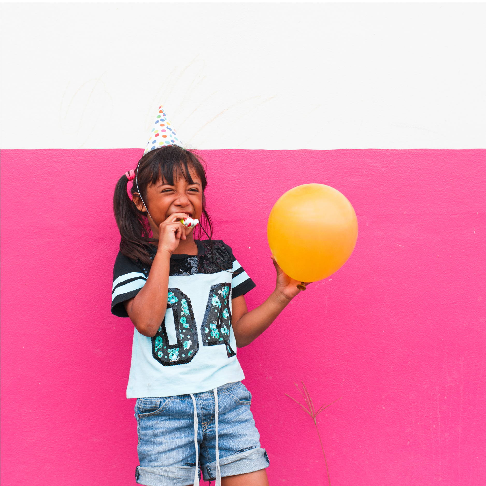 A young Honduran girl standing in front of a pink wall wears a part hat while holding a balloon and laughing.