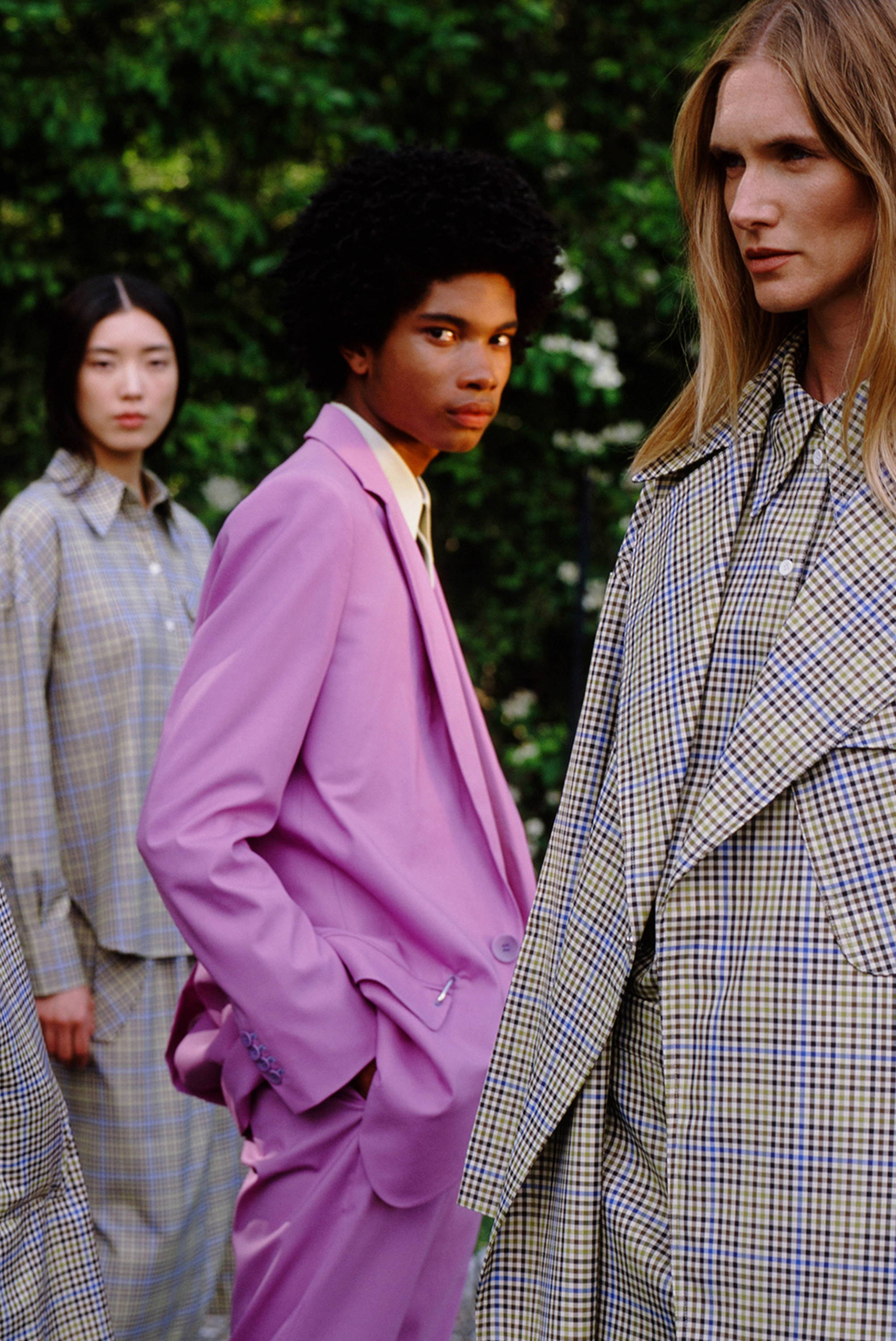 Male model wearing purple suit. Female model wearing recycled check pieces from Resort 2020.