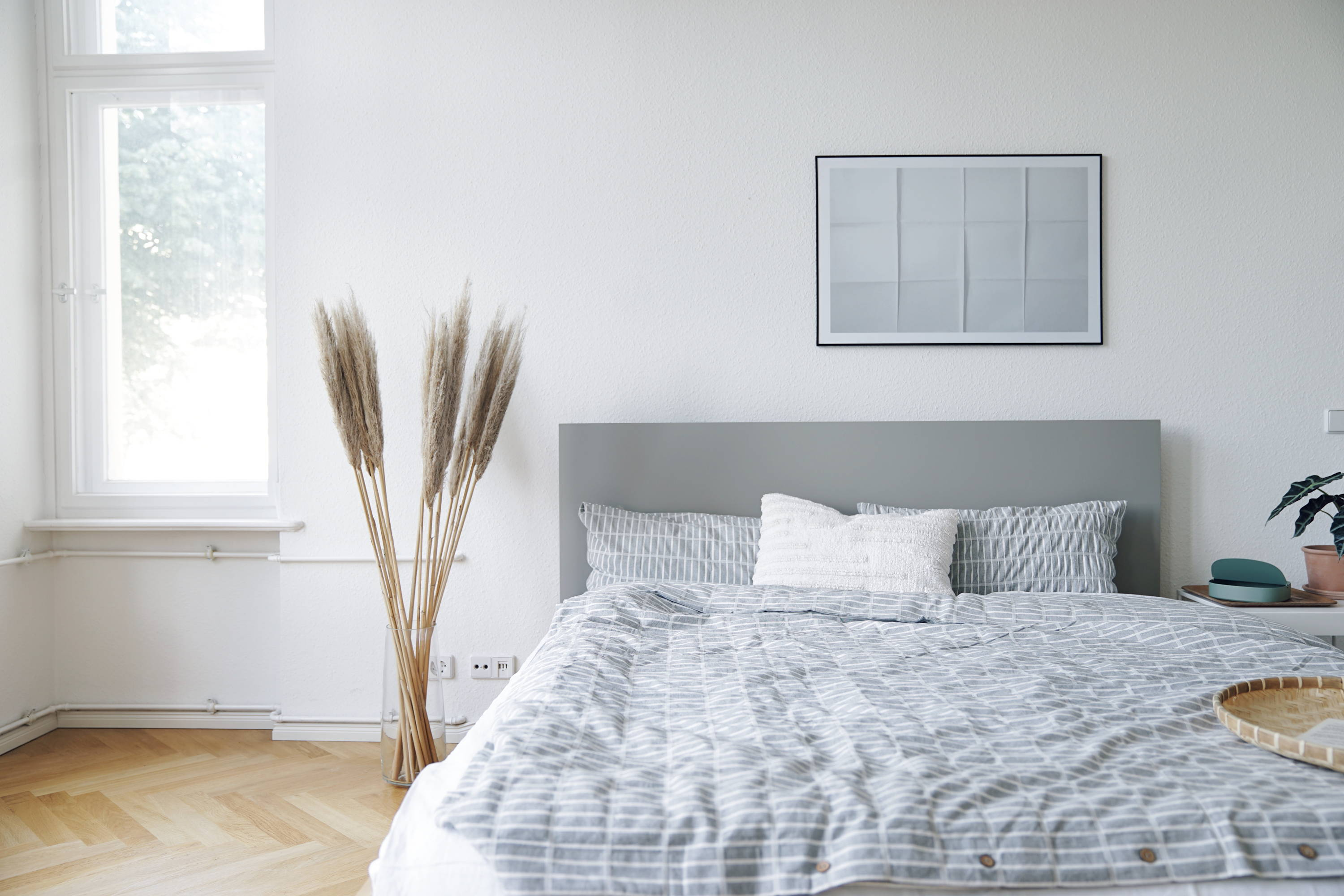Lagom style bedroom with grey and white bedding, wall art, herringbone floor