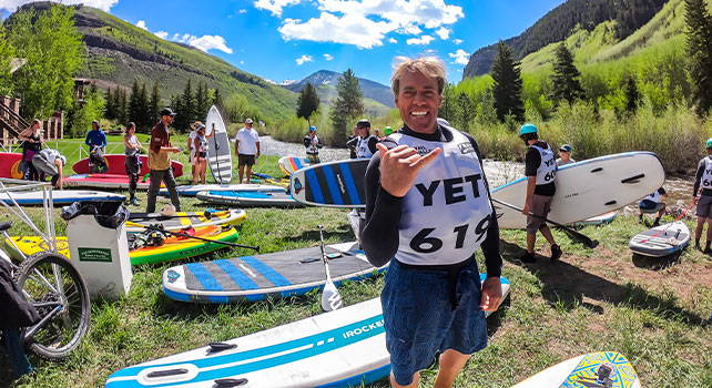 Stand up paddle boarders by gear in mountain valley. Photo Credit: Jon Resnick