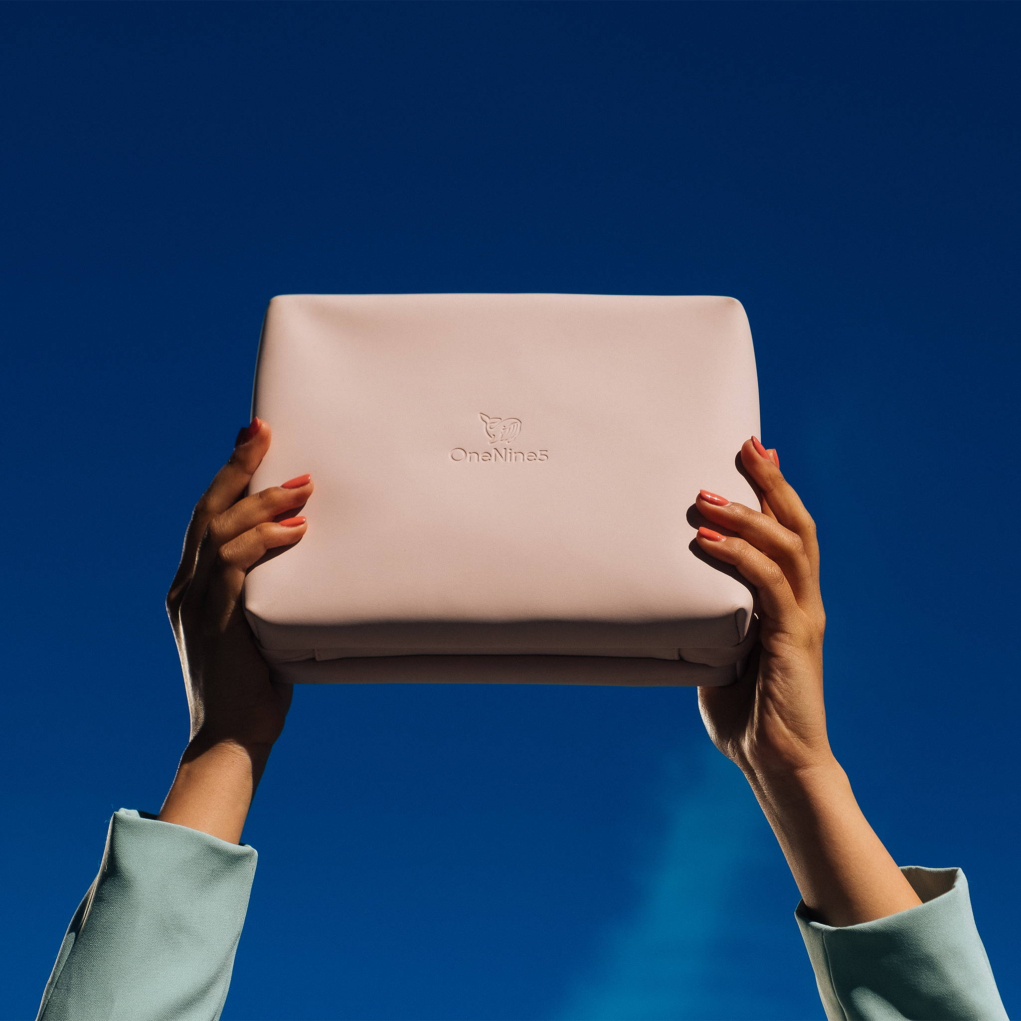 Female hands holding the Komodo Pink Eco Travel Wash Bag in the air. With a bright blue sky in the background.