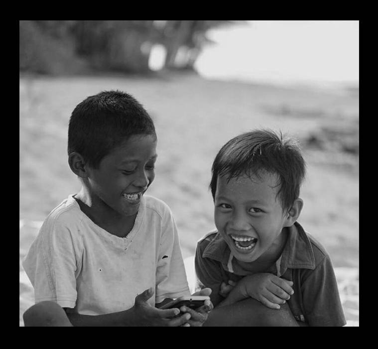 Two young boys laughing at their smartphone