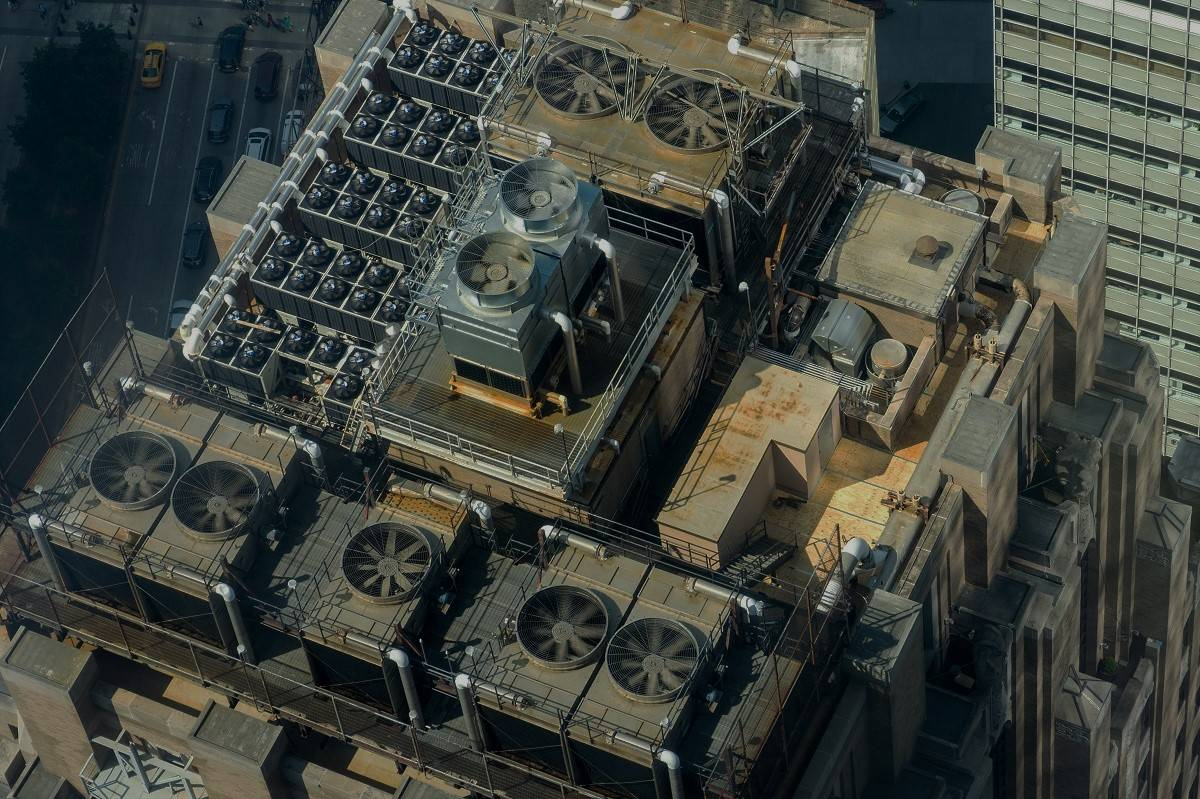 A rooftop image of large air conditioning units and fans on the top of an office block