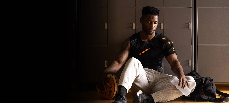 Man using Myovolt Shoulder sitting against basketball lockers