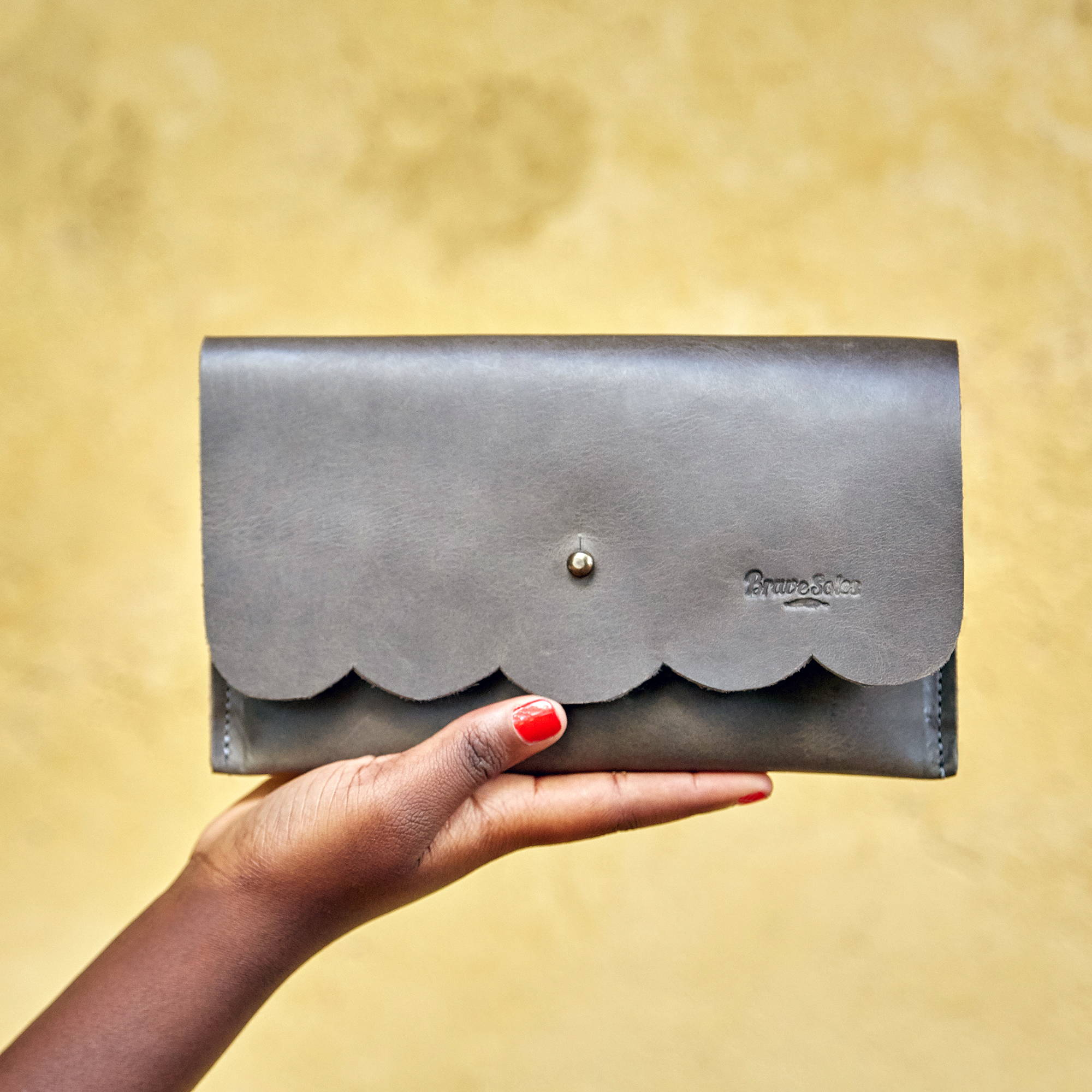 A hand holding up a light grey travel clutch from Brave Soles made of recycled tires.