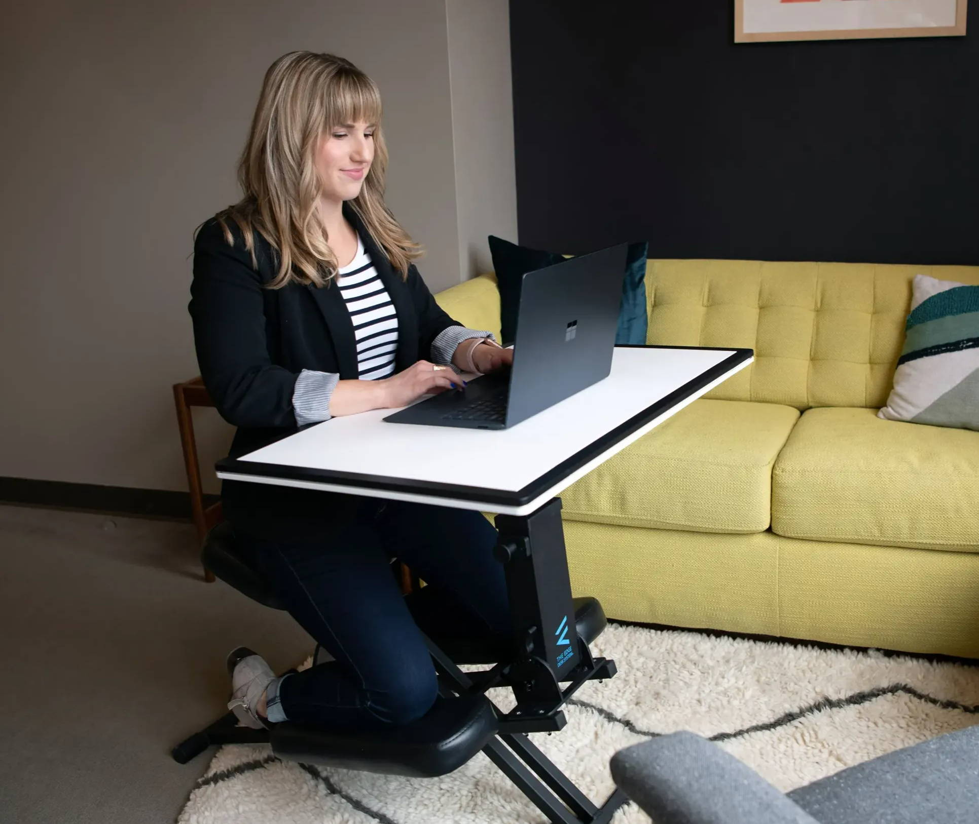 Woman using The Edge Desk, the best adjustable ergonomic kneeling desk for the office and back pain in her living room.