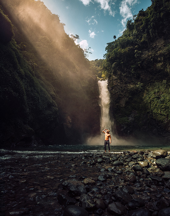 man standing by base of waterfall in tropical forest