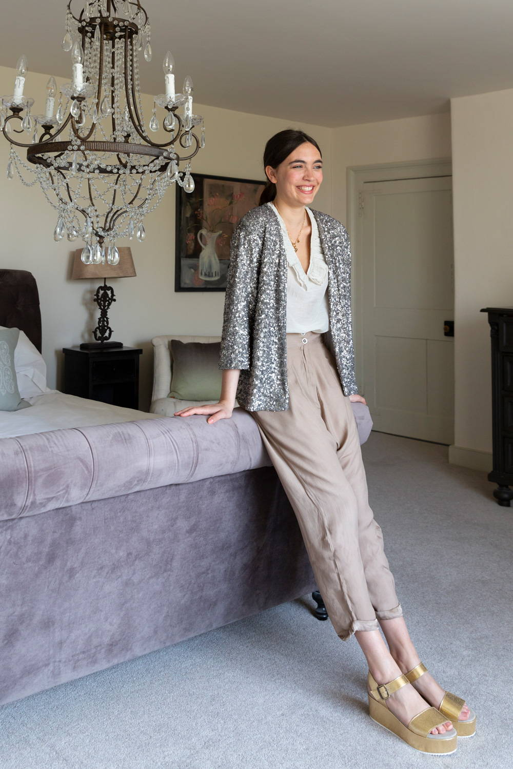Model wearing neutral trousers with sequin jacket.