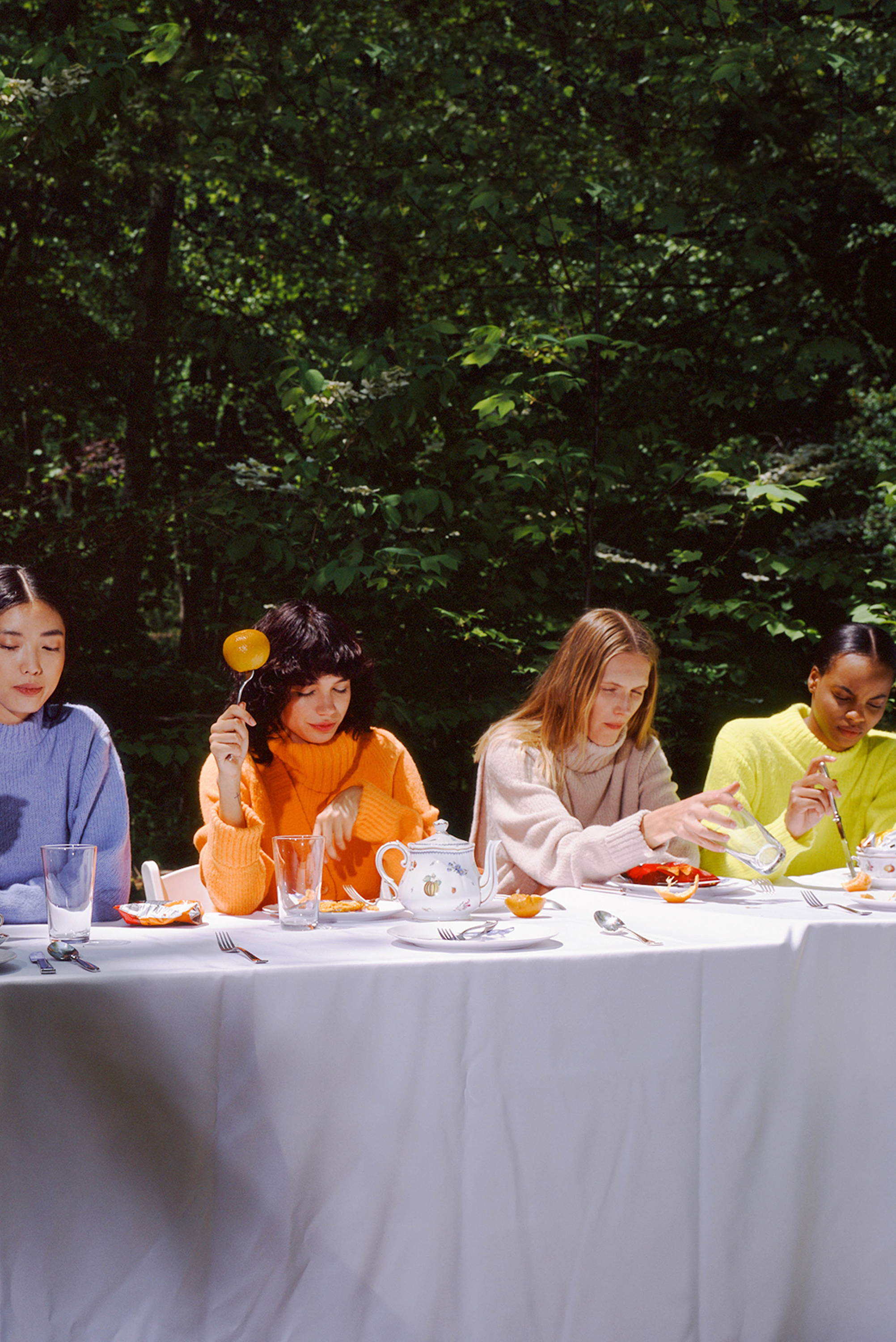 Models lined up sitting at table. All wearing sweaters and eating a mix of snack like apples, chips and oranges.
