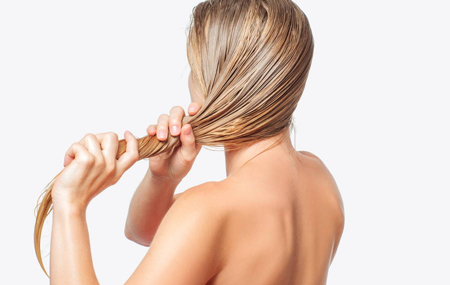 woman applying castor oil to her hair