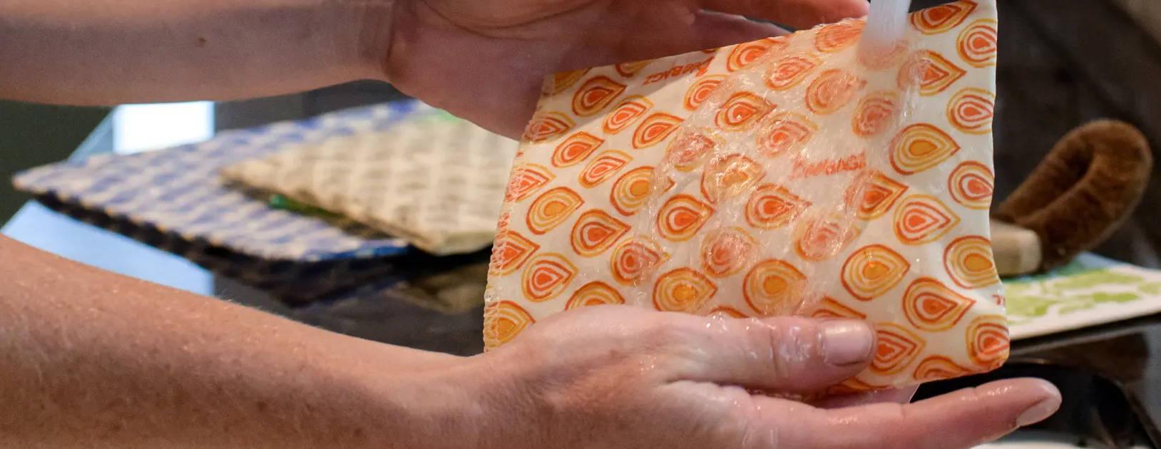 BeeBAGZ® Reusable beeswax wrap baggies being rinsed in water.