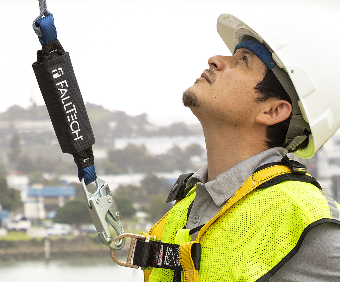 Construction worker looking up, wearing a ViewPack Energy Absorbing lanyard attached to the front D-ring of his harness
