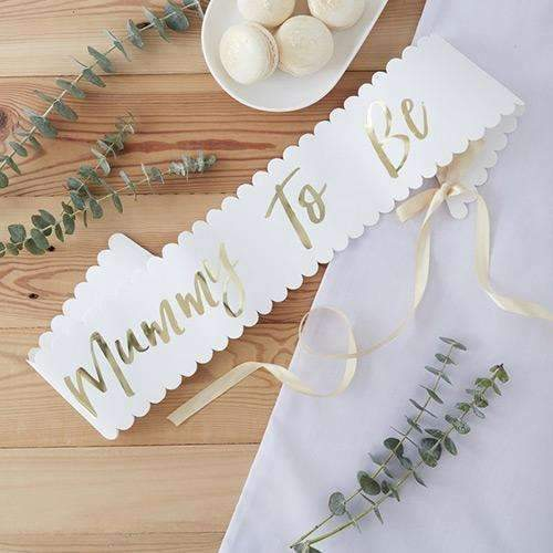 A photo of a cream 'Mummy to Be' sash laid out on the table with gold lettering and pale ribbon