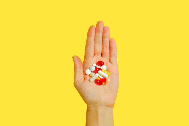 Person Holding Medicine Pills In Hand