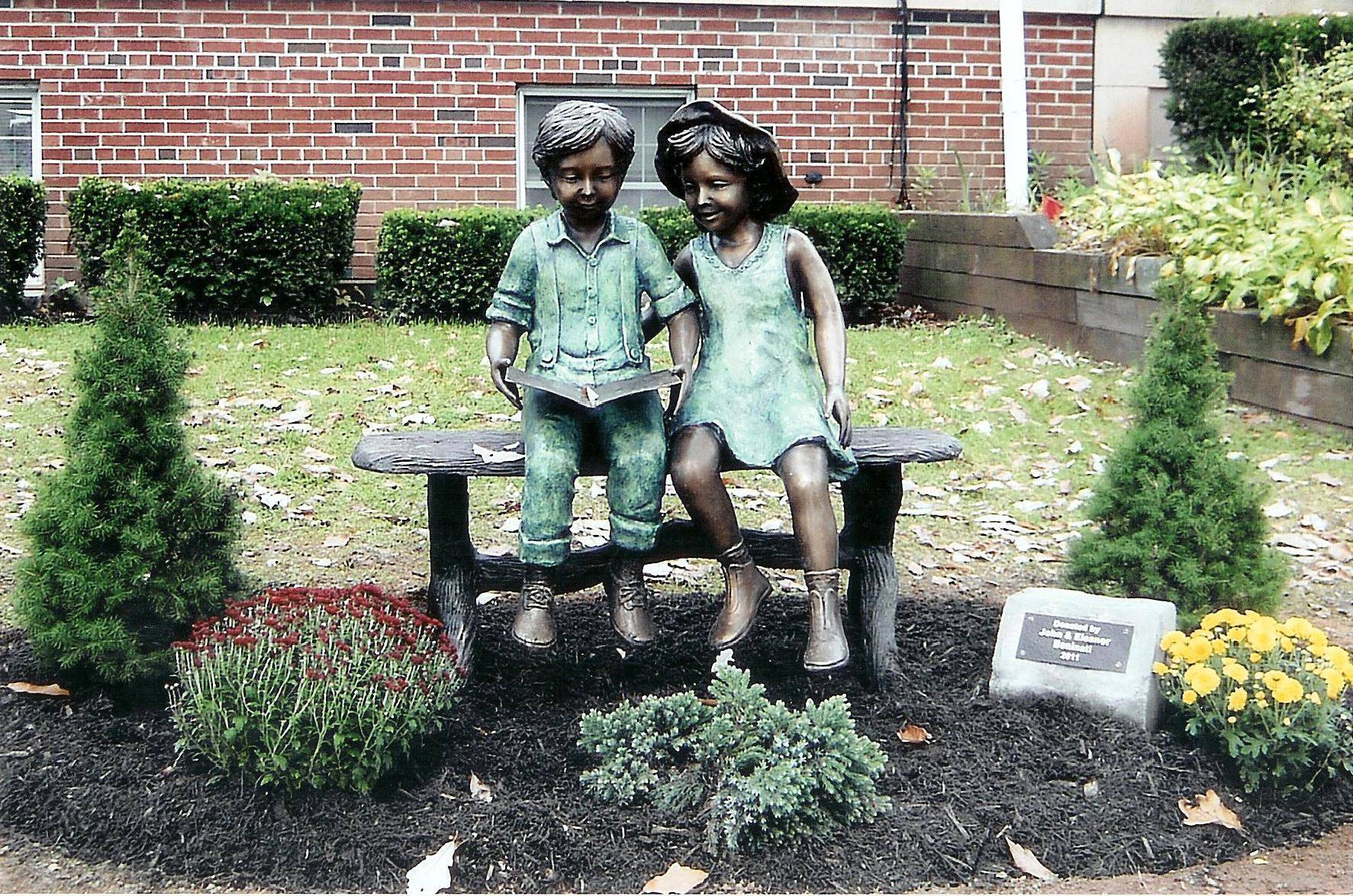 Bronze statue of children reading at the library