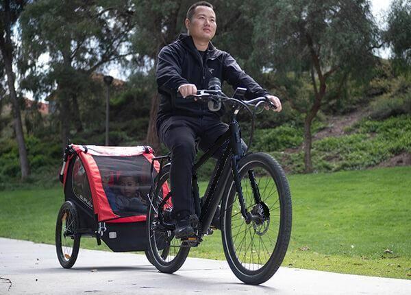 man rides pace 500 ebike on bike path pulling trailer