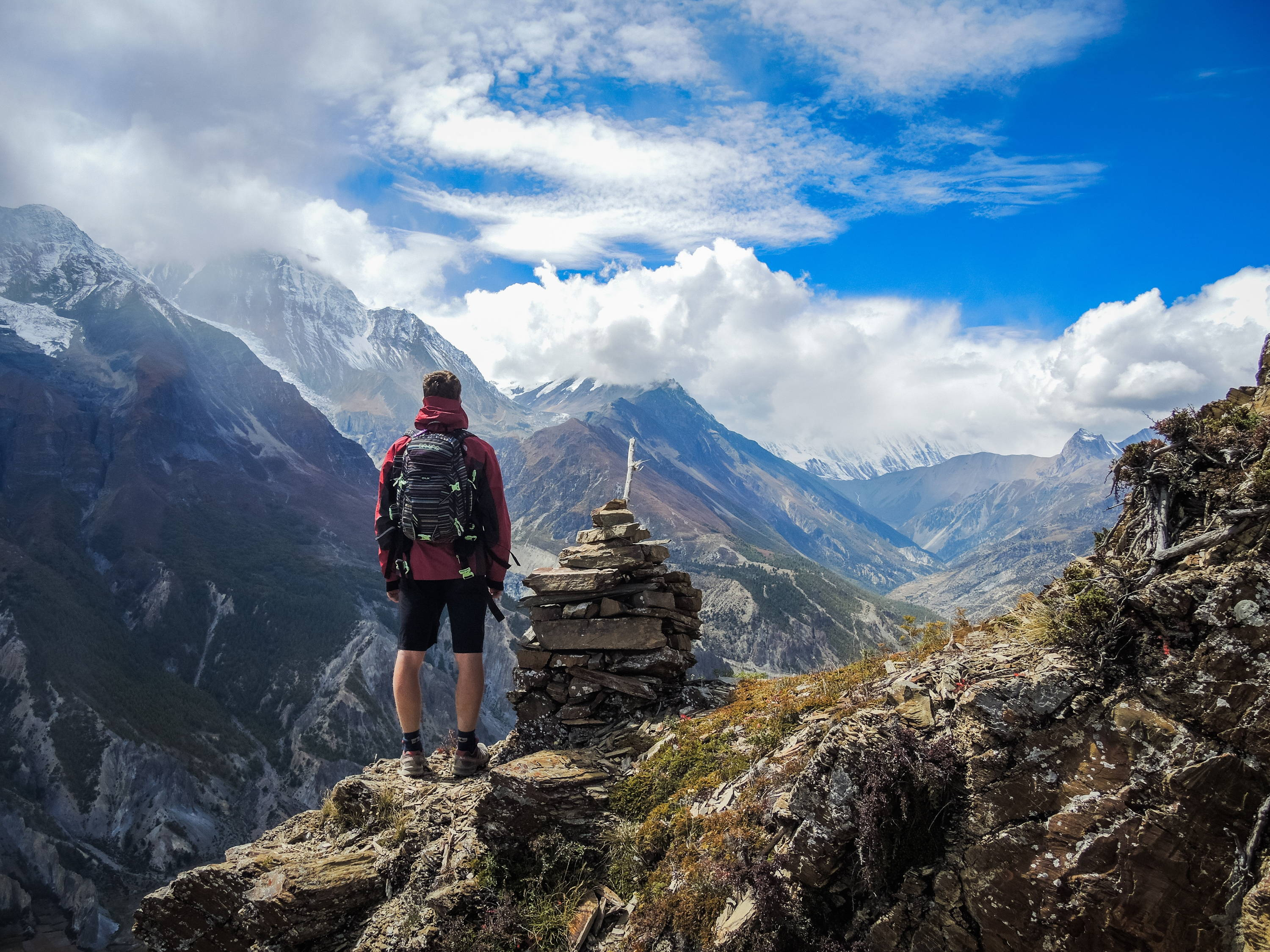 Adventure Vacations For Adrenaline Junkies: Man looks in amazement at valley and mountain setting in Nepal.