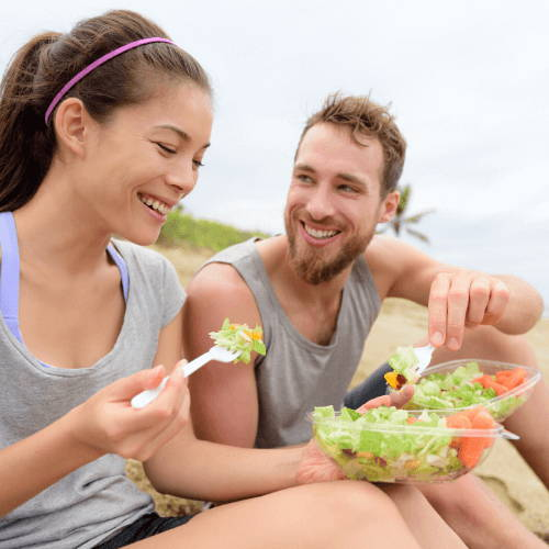 Girl and Guy Eating Vegetables