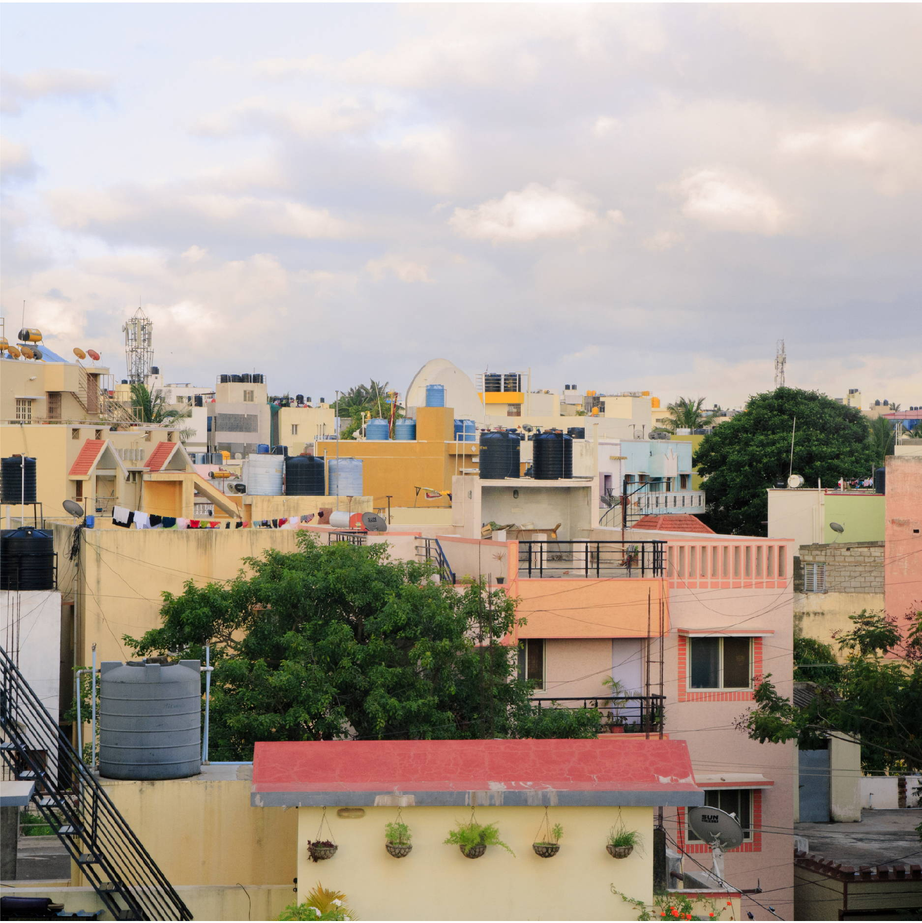 The sun sets across a crowded and colorful Indian neighborhood in Bangalore India.