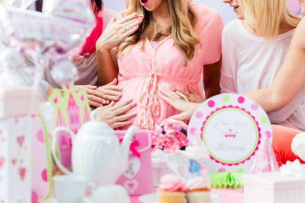 guests touching pregnant baby belly at baby shower
