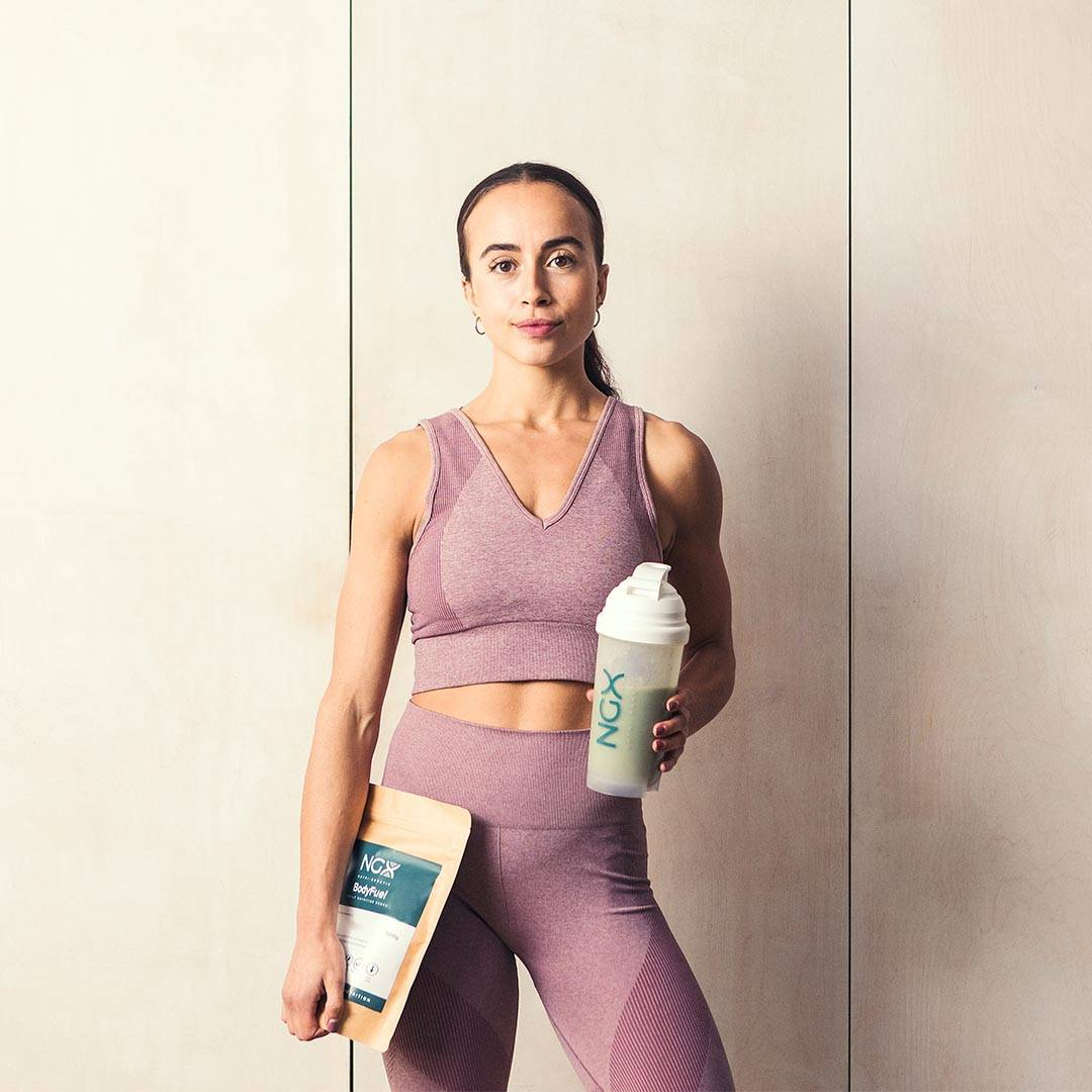 Tanned women in pink gym wear holding NGX BodyFuel