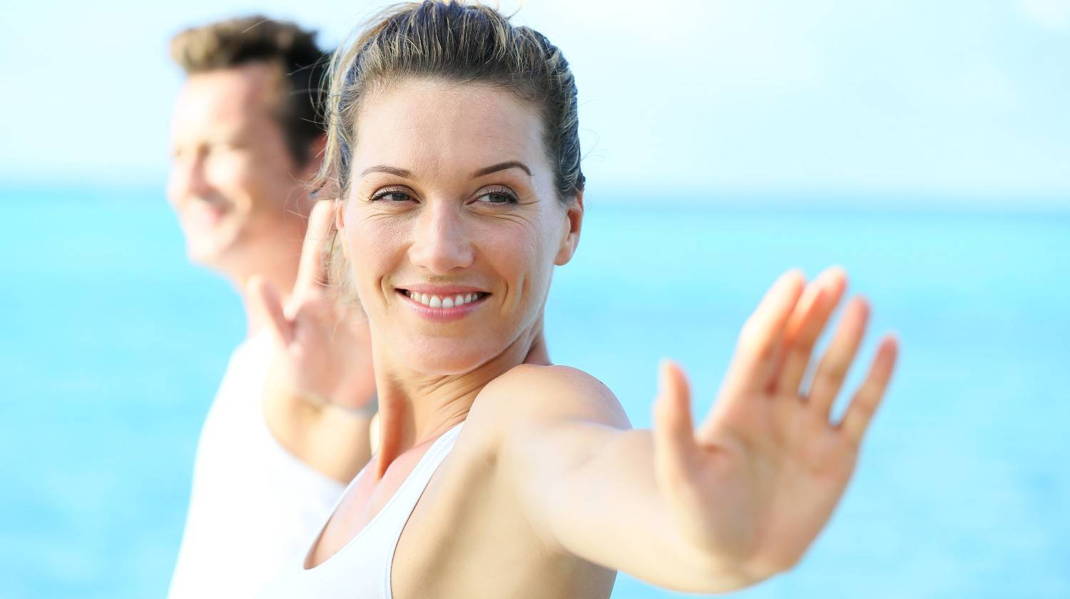 Couple doing yoga and relaxation exercises by the sea   Silica Health Benefits – Detox, Skin Health, and More   Silica Benefits   what is silica used for   Featured
