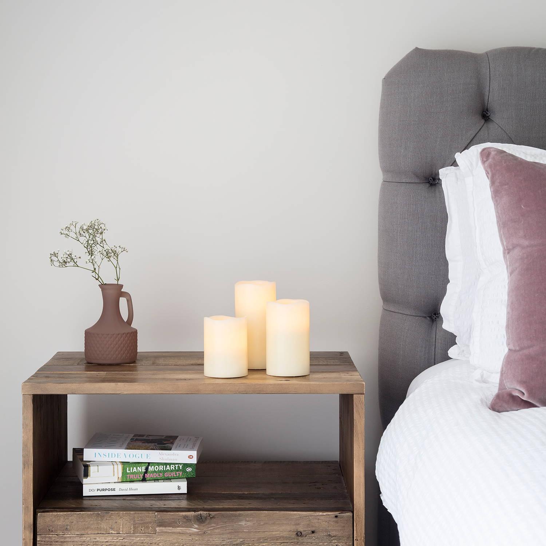 Schlafzimmer mit Bett, LED Kerzen, Vase und Büchern.