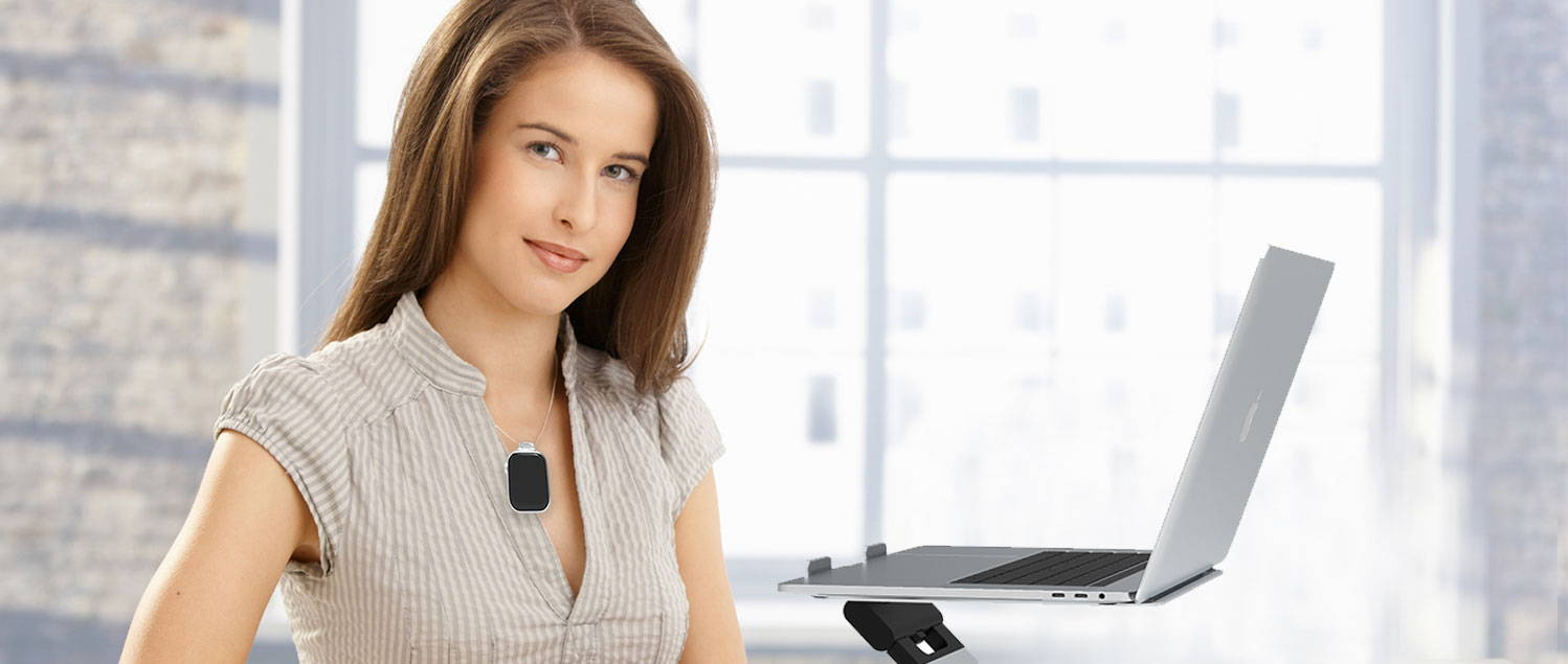 Lady wearing apple watch on neck using it as a minder. Looking at computer on the laptop stand.
