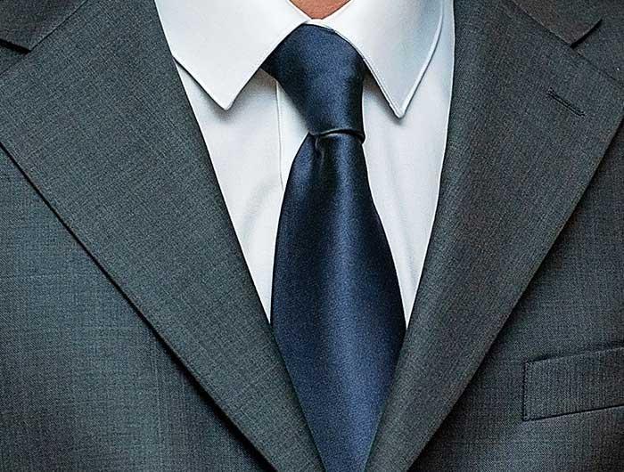 Navy blue necktie worn with a gray suit