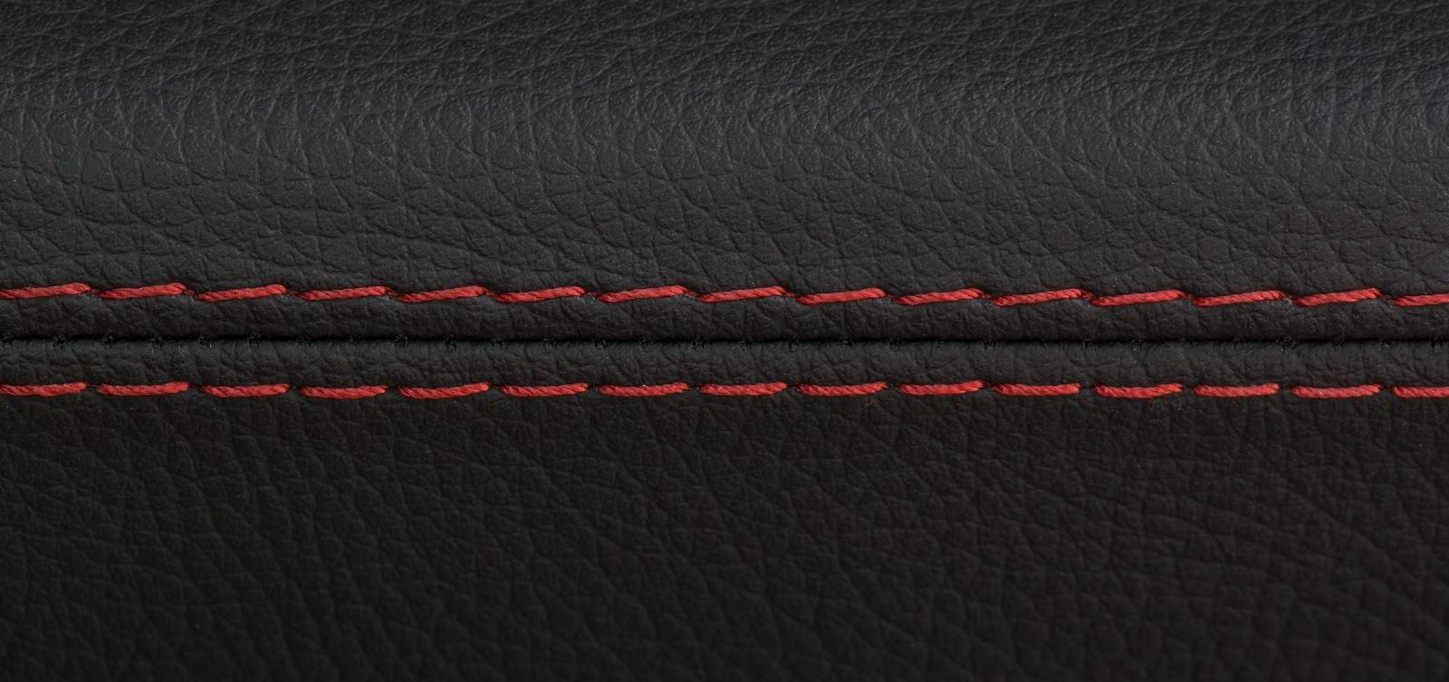 : A black leather car seat with a red seam