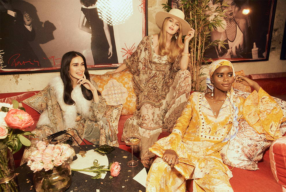 Models wearing CAMILLA paisley, floral layered outfits in bar with cocktails
