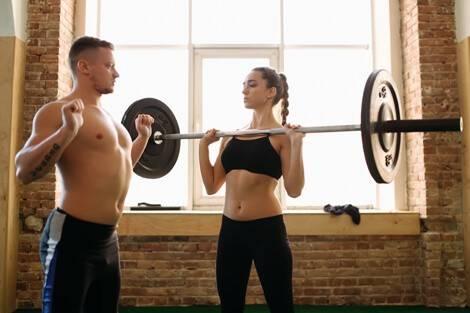 Mann gibt Frau Anleitung fürs Schulterdrücken
