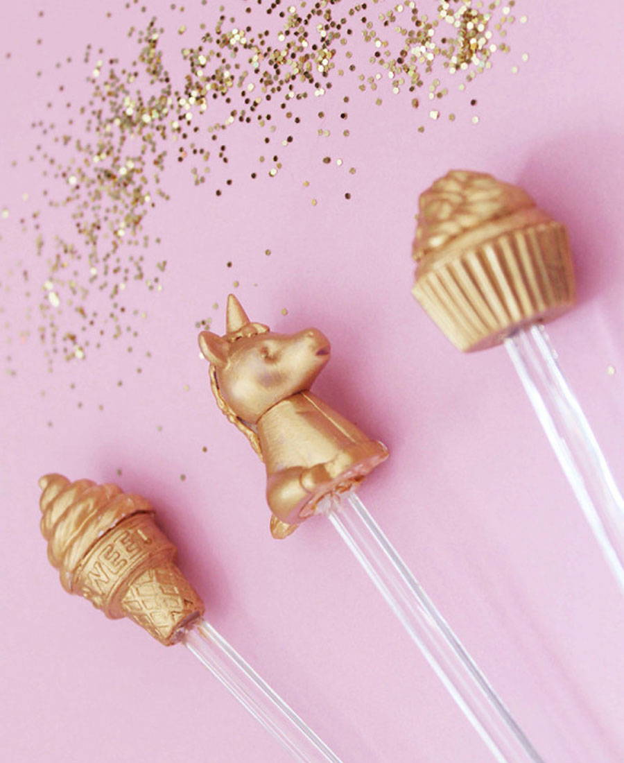 Gold unicorn, cupcake and ice cream figures on top of acrylic stirrers.