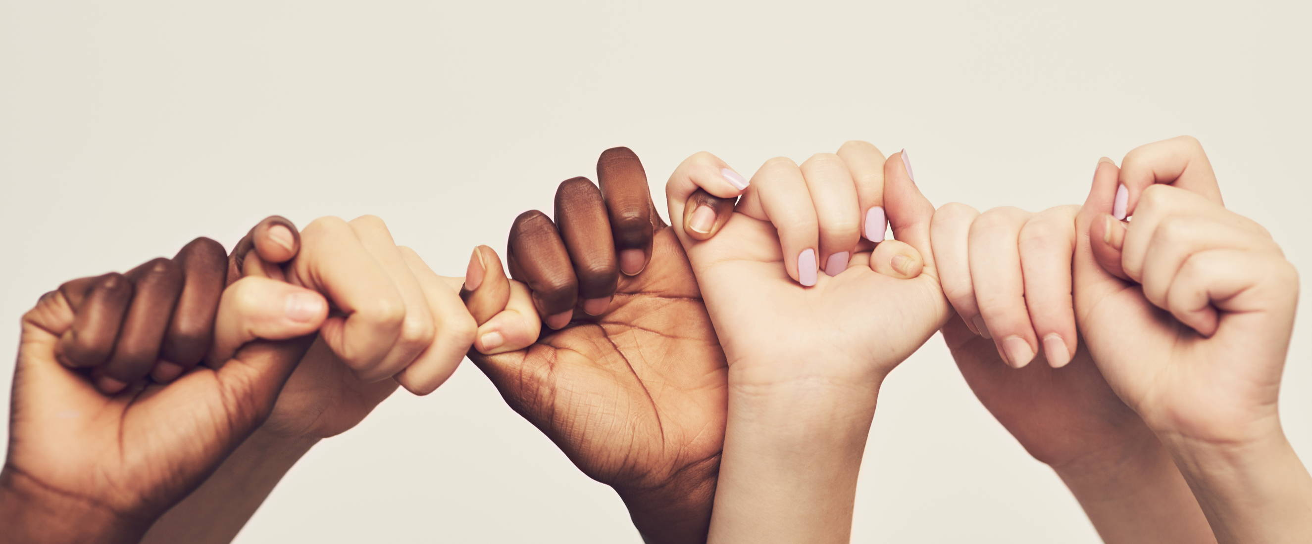 Hands of different skin tones linking fingers to make a promise.
