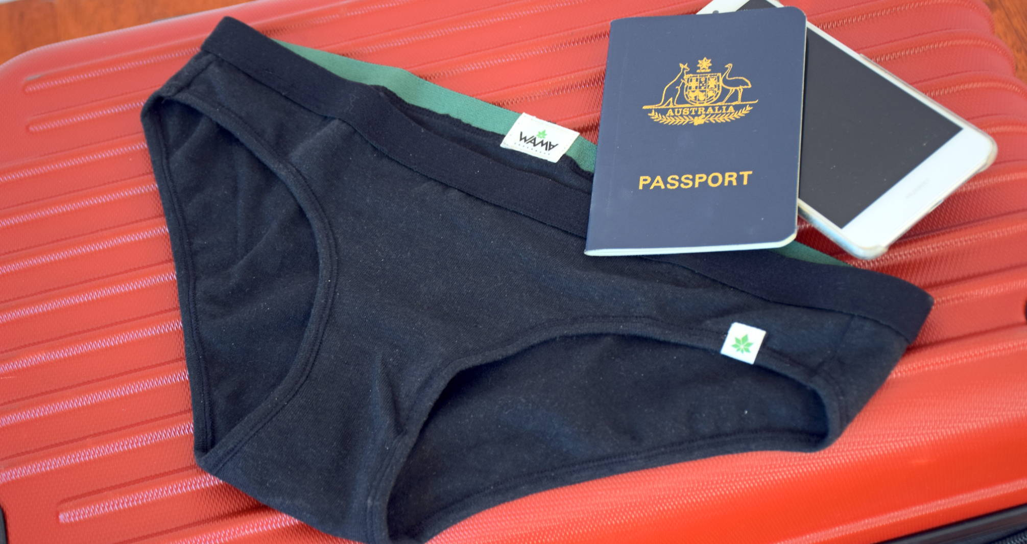 A pair of WAMA hemp travel underwear sits atop a red suitcase with a passport and cell phone.