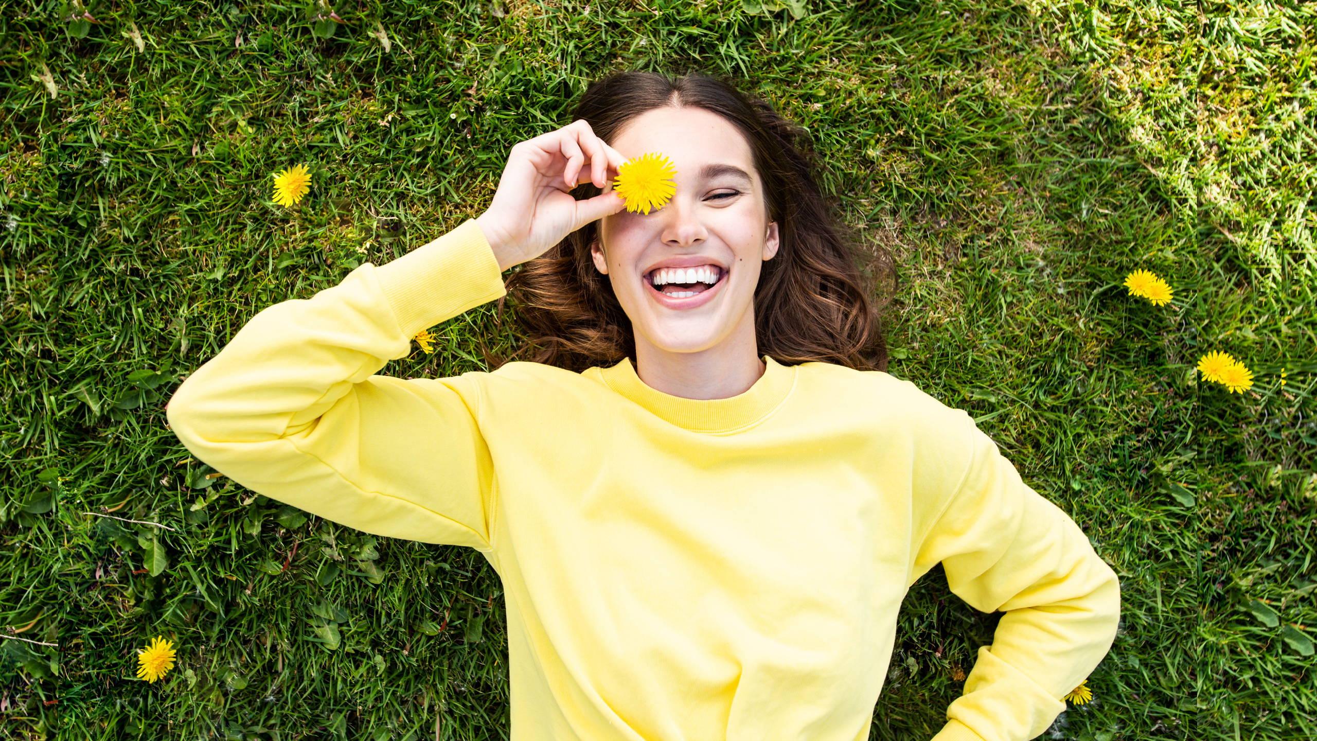Women laying in grass wearing yellow sweater