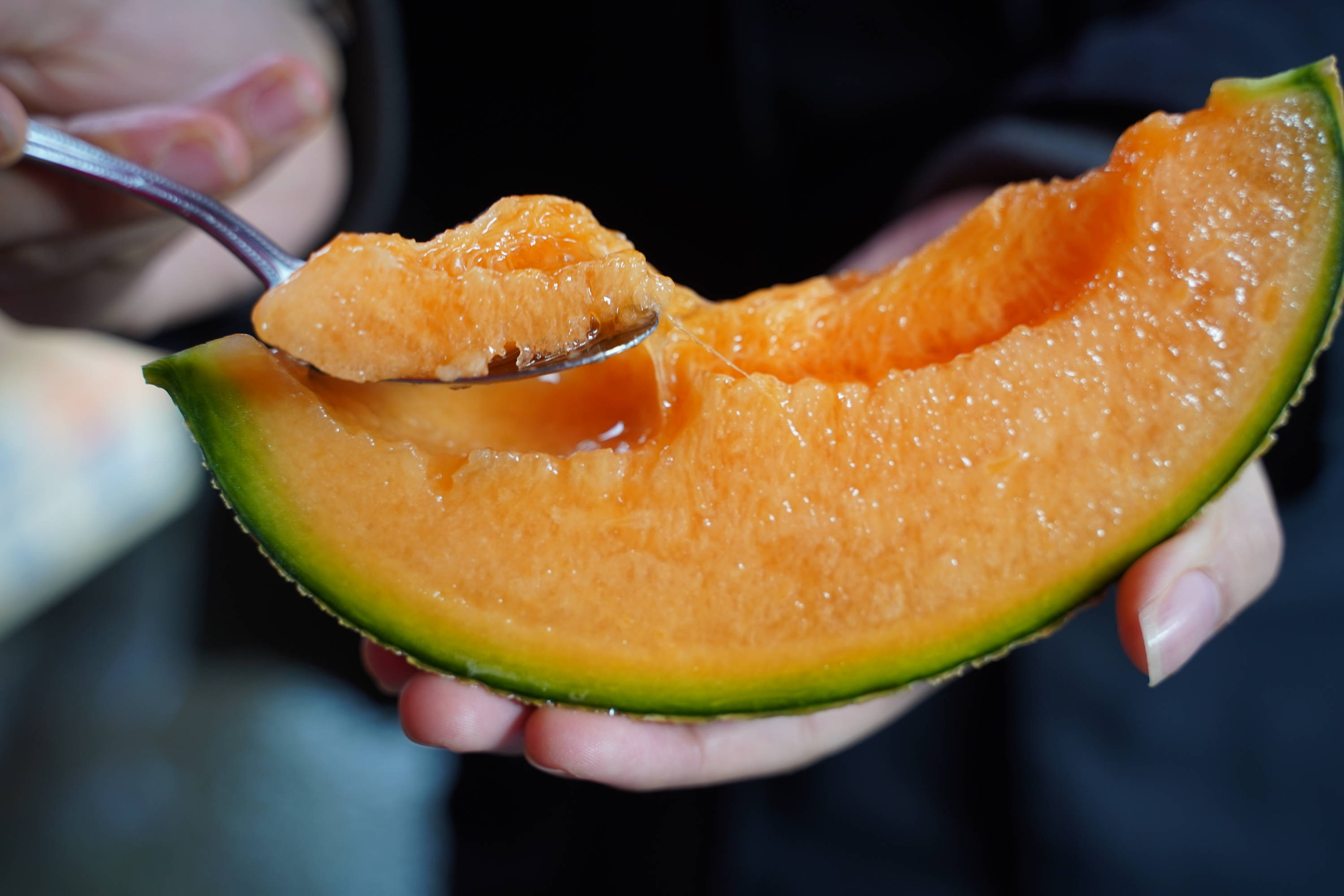 This is a picture of a slice of cantaloupe being spooned by a person.