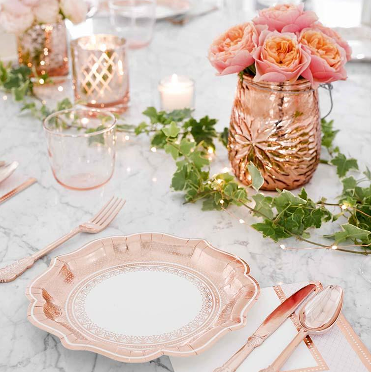 A photo of a wedding place setting with a rose gold paperplate and tableware from Party Porcelain, with a backdrop of rose gold tealight candle holders, flowers in a jug, and leaf garland and string lights for the wedding table