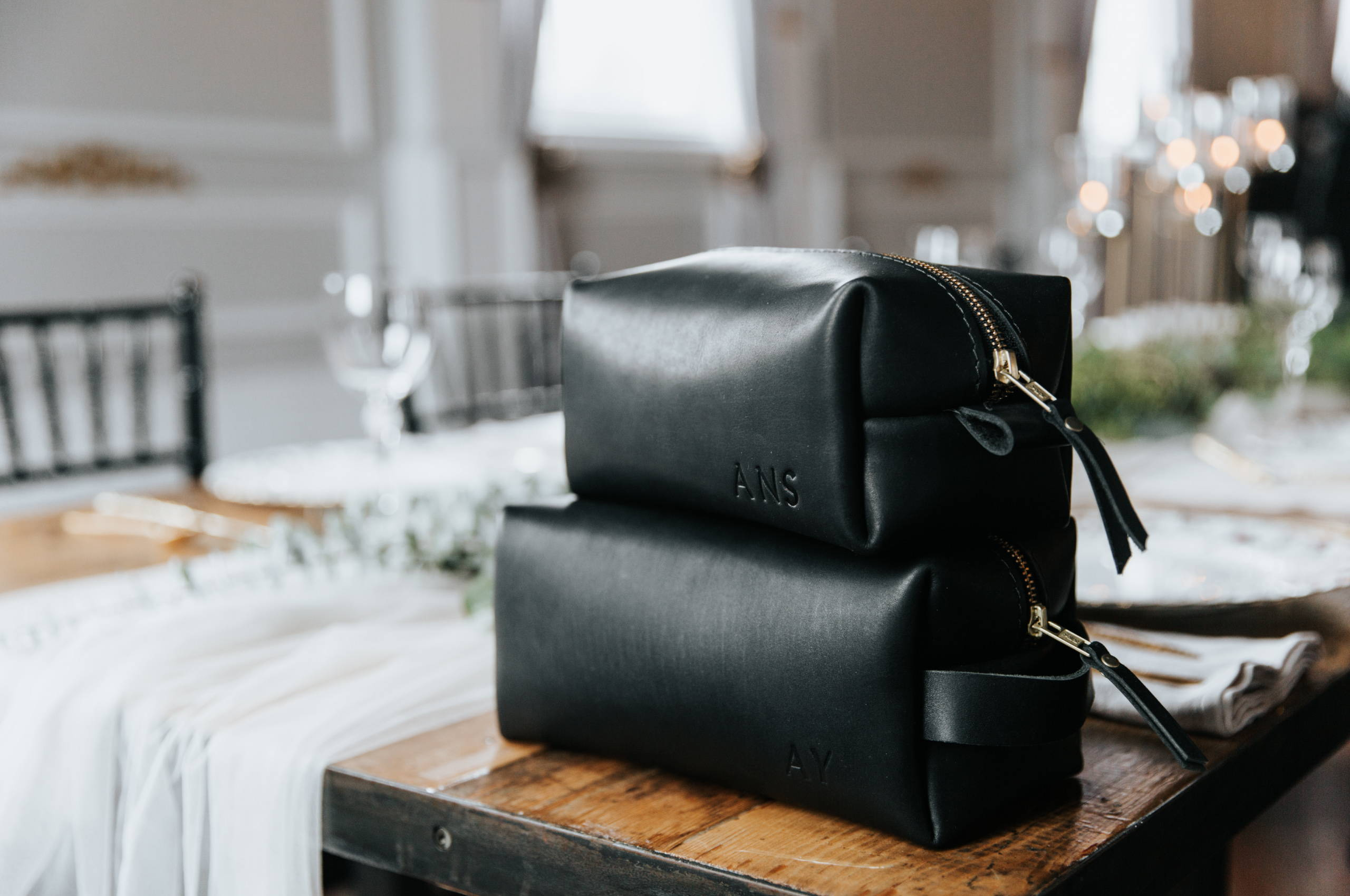 two handmade black leather dopp kits made by portland leather goods stacked on a well decorated dinner table
