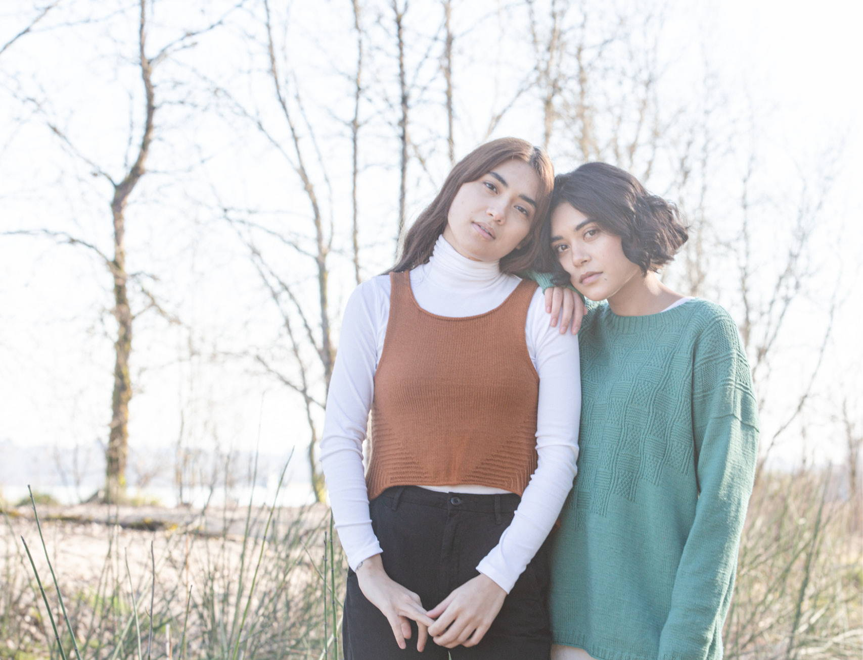 Byssa tank and Bewick pullover on live models leaning on each other on a wooded a river shore.