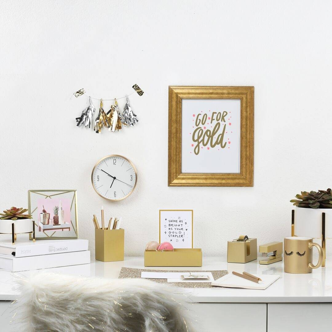 a white desk with a gold desk set, gold mug, a gold picture frame, and metallic tassels on the wall