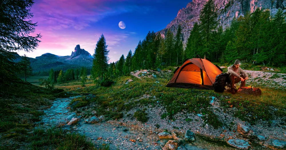 A backpacking hiker set up at camp around a fire with the moon in the sky